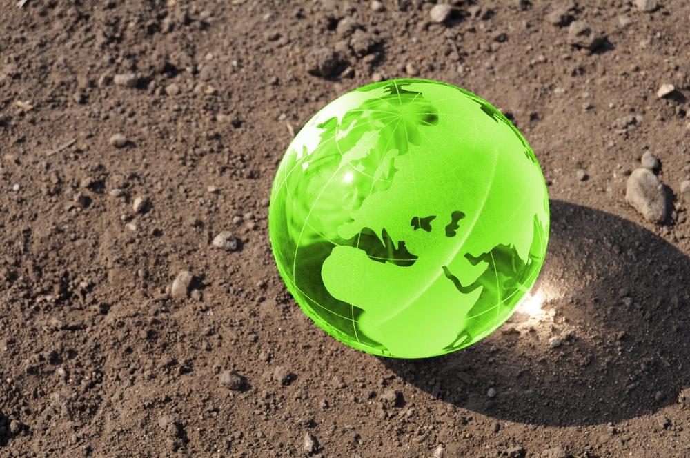 Globo terráqueo verde sobre suelo de tierra